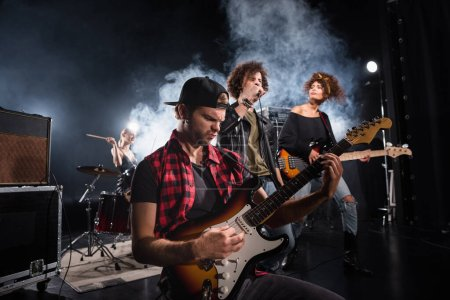 Photo for KYIV, UKRAINE - AUGUST 25, 2020: Rock band musician playing bass guitar sitting near curly vocalist and guitarist with smoke and female drummer on background - Royalty Free Image