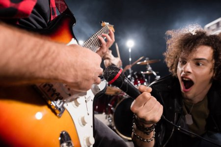Photo for KYIV, UKRAINE - AUGUST 25, 2020: Curly vocalist with open mouth holding microphone near guitar strings with backlit on blurred background - Royalty Free Image