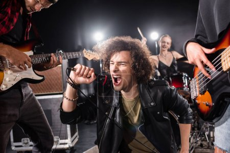 Photo for KYIV, UKRAINE - AUGUST 25, 2020: Curly vocalist shouting in microphone while sitting near guitarists with backlit and blurred female drummer on background - Royalty Free Image
