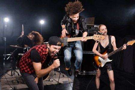 KYIV, UKRAINE - AUGUST 25, 2020: Vocalist shouting in microphone while leaning forward near guitarist jumping up during rock band show on blurred background