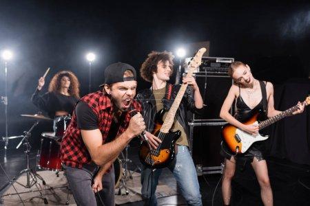 KYIV, UCRANIA - 25 de agosto de 2020: Hombre cantando mientras se inclina hacia adelante cerca de guitarristas con retroiluminación y baterista femenina sobre fondo borroso