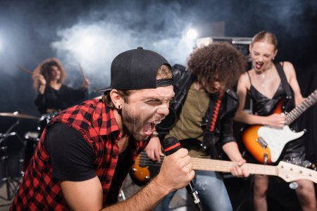 KYIV, UKRAINE - AUGUST 25, 2020: Vocalist screaming in microphone while leaning forward near rock band musicians on blurred background