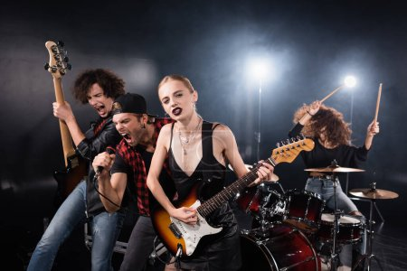 KYIV, UKRAINE - AUGUST 25, 2020: Blonde woman looking at camera while playing electric guitar standing near musicians shouting and drummer on black