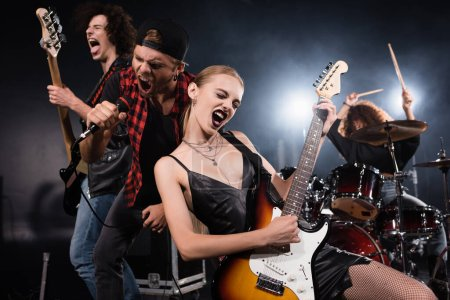 KYIV, UKRAINE - AUGUST 25, 2020: Blonde woman playing electric guitar while shouting with vocalist and guitarist with female drummer on blurred background