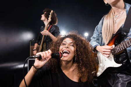 KYIV, UKRAINE - AUGUST 25, 2020: Happy curly woman with microphone singing near rock band guitarists with back light on black