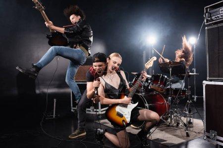 Photo pour KYIV, UKRAINE - 25 AOÛT 2020 : Le chanteur crie au microphone tout en se penchant vers l'avant près du guitariste sautant vers le haut et la femme assise sur le genou avec rétro-éclairé sur noir - image libre de droit