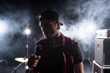 Photo for Rock band vocalist holding microphone, with smoke and backlit on blurred background - Royalty Free Image