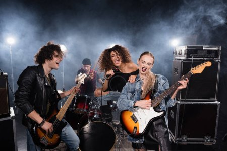 Photo for KYIV, UKRAINE - AUGUST 25, 2020: Woman with leg on drum kit singing and leaning on female guitarist with smoke and backlit on background - Royalty Free Image