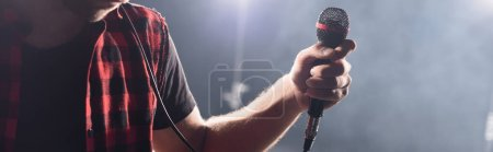 Cropped view of vocalist of rock band holding microphone on blurred background, banner