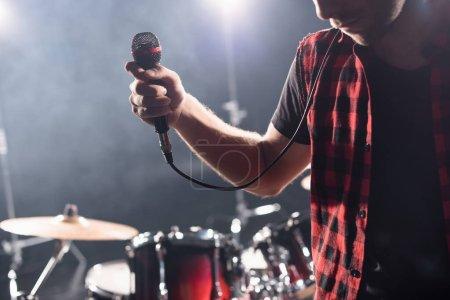 Foto de Vista recortada del vocalista con micrófono con kit de batería borrosa en el fondo - Imagen libre de derechos