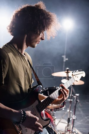 Photo for KYIV, UKRAINE - AUGUST 25, 2020: Curly musician playing bass guitar while standing near drum kit with backlit on blurred background - Royalty Free Image