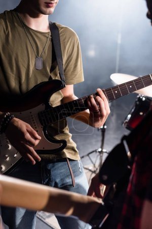 Photo for KYIV, UKRAINE - AUGUST 25, 2020: Cropped view of rock band musician playing bass guitar with pick with blurred guitarist on foreground - Royalty Free Image