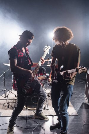 Photo for KYIV, UKRAINE - AUGUST 25, 2020: Rock band musicians playing electric guitars near drum kit with back light on background - Royalty Free Image