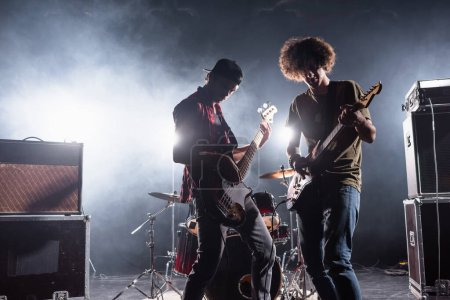 KYIV, UKRAINE - AUGUST 25, 2020: Rock band musicians playing bass guitars near drum kit and combo amplifiers with smoke and backlit on background