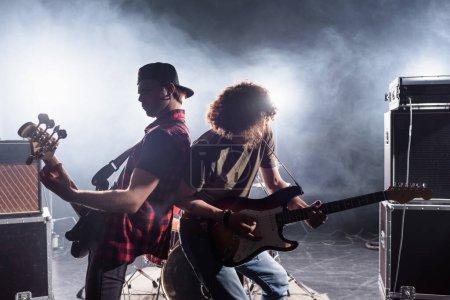 KYIV, UCRANIA - 25 DE AGOSTO DE 2020: Músicos de bandas de rock que tocan las guitarras eléctricas cerca de amplificadores combinados con humo en el fondo