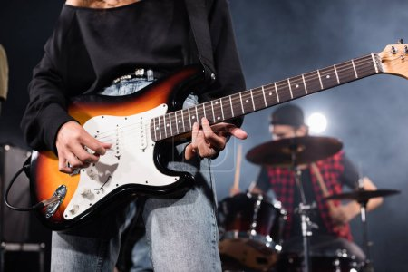Photo for KYIV, UKRAINE - AUGUST 25, 2020: Female musician playing electric guitar with blurred drummer on background - Royalty Free Image