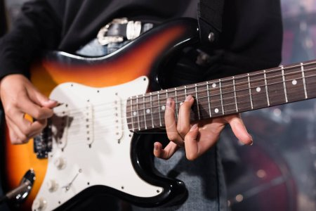 Photo for KYIV, UKRAINE - AUGUST 25, 2020: Cropped view of female musician playing electric guitar on blurred background - Royalty Free Image