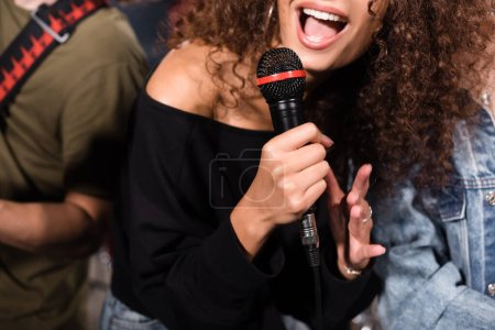Cropped view of curly female vocalist with microphone singing near rock band musicians on blurred background