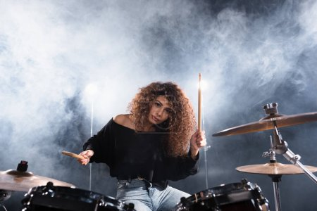 Female musician with drumsticks playing on drum kit while looking at camera with smoke on background