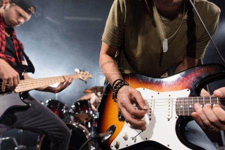 KYIV, UCRANIA - 25 de agosto de 2020: Músico de banda de rock inclinado y tocando la guitarra eléctrica con pico con músicos borrosos en el fondo