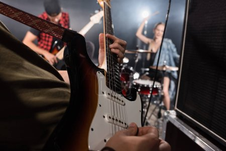 KYIV, UKRAINE - AUGUST 25, 2020: Close up view of man playing electric guitar near combo amplifiers with blurred drummer and guitarist on background