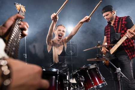 KYIV, UKRAINE - AUGUST 25, 2020: Blonde woman with outstretched hands screaming while sitting at drum kit near guitarist with backlit on blurred foreground