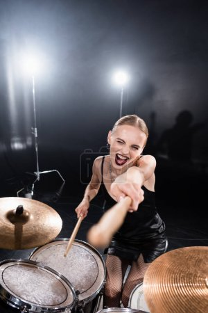 High angle view of excited blonde pointing with drumstick while sitting at drum kit with backlit on blurred foreground