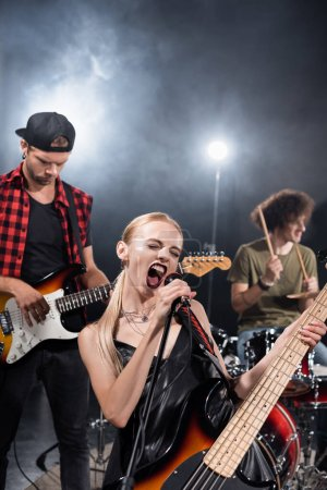 KYIV, UKRAINE - AUGUST 25, 2020: Female vocalist of rock band shouting in microphone near guitarist with backlit and blurred drummer on background