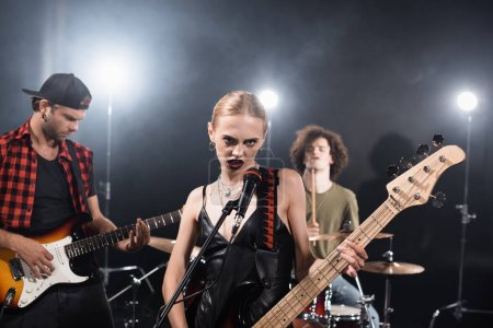 KYIV, UKRAINE - AUGUST 25, 2020: Angry woman with electric guitar looking at camera near guitarist with backlit and blurred drummer on background