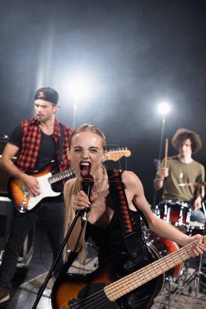 KYIV, UCRANIA - 25 de agosto de 2020: Vocalista femenina de la banda de rock con guitarra eléctrica gritando en el micrófono con músicos retroiluminados y borrosos en el fondo