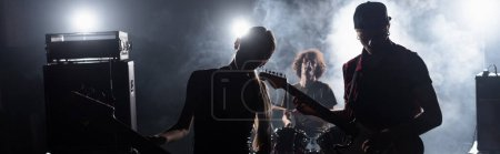 Photo for KYIV, UKRAINE - AUGUST 25, 2020: Rock band guitarists standing near combo amplifiers and drummer sitting at drum kit with backlit and smoke on background, banner - Royalty Free Image