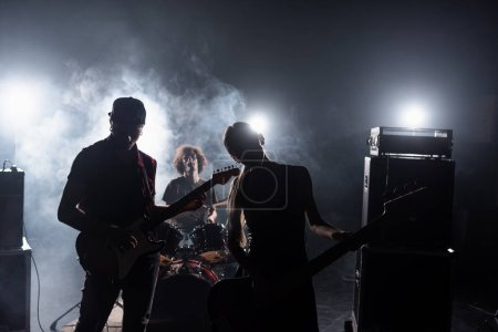 KYIV, UKRAINE - AUGUST 25, 2020: Rock band guitarists standing near combo amplifiers and drummer sitting at drum kit with backlit and smoke on background
