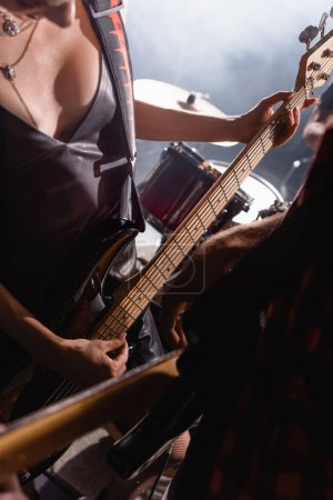 Photo for KYIV, UKRAINE - AUGUST 25, 2020: Woman touching guitar strings standing near drums with blurred guitarist on foreground - Royalty Free Image