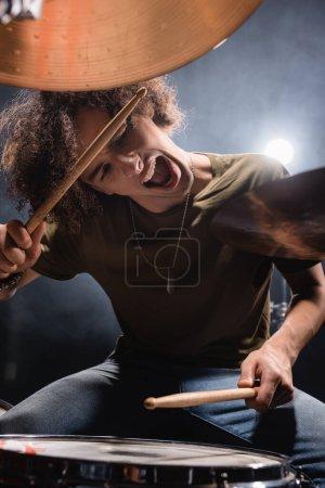 Foto de Músico rizado gritando mientras toca el tambor con palos de batería en primer plano borroso - Imagen libre de derechos