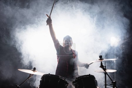Drummer with hand in air, holding drumsticks while sitting at drum kit with smoke on black