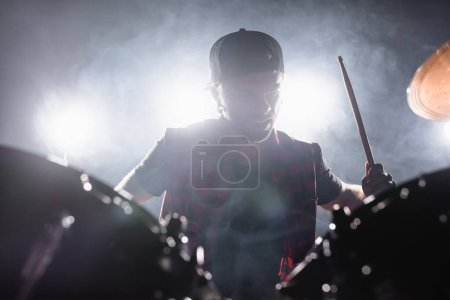 Rock band musician with drumstick playing drums with smoke and backlit on background
