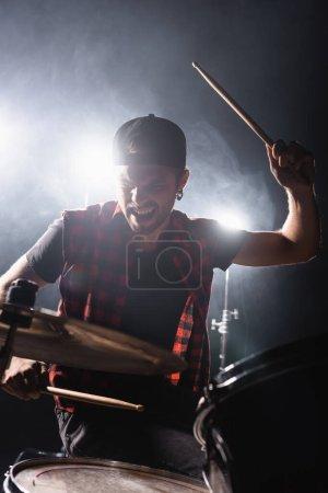 Photo pour Tambour de groupe de rock tenant le tambour et jouant de la batterie avec contre-jour et fumée sur le fond - image libre de droit