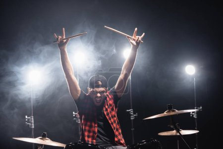 Photo for Angry drummer showing rock signs yelling, while sitting at drum kit with backlit on background - Royalty Free Image