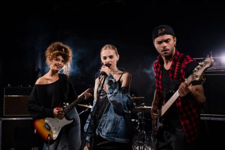 KYIV, UKRAINE - AUGUST 25, 2020: Female singer of rock band standing near musicians with electric guitars on black