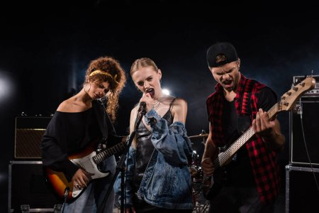 KYIV, UKRAINE - AUGUST 25, 2020: Blonde vocalist of rock band singing near musicians with bass guitars with backlit on black