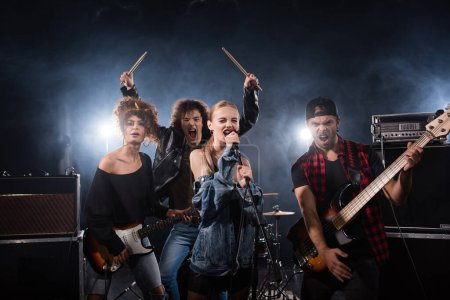 Photo for KYIV, UKRAINE - AUGUST 25, 2020: Rock band musicians yelling while holding musical instruments with backlit on black - Royalty Free Image