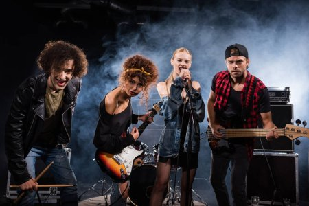 Photo for KYIV, UKRAINE - AUGUST 25, 2020: Female vocalist singing, while standing near rock band members with bass guitars and drumsticks, with smoke on black - Royalty Free Image