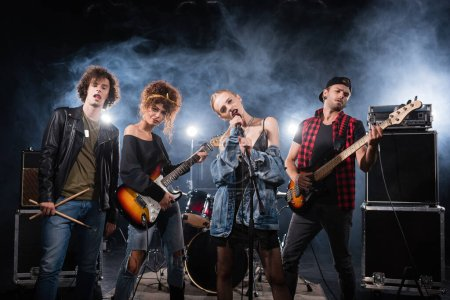 KYIV, UKRAINE - AUGUST 25, 2020: vocalist of rock band singing near musicians with bass guitars and drumsticks with smoke on black