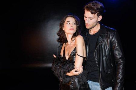 Photo pour Femme sexy en robe avec bandoulière coulissante, regardant son petit ami passionné sur noir - image libre de droit
