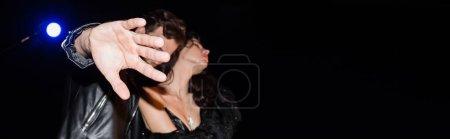 Photo pour Homme en cuir veste caméra de fermeture avec la main sur fond flou avec rétro-éclairé, bannière - image libre de droit