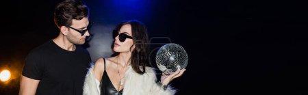 Photo pour Femme brune avec boule disco regardant l'homme en lunettes avec rétro-éclairage sur noir, bannière - image libre de droit