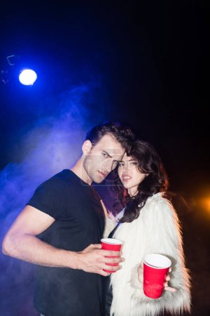 Irritated young adult couple looking at camera, holding plastic cups, while embracing with smoke and backlit on black