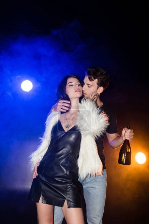 Passionate man with champagne bottle touching woman neck wearing white jacket and dress with backlit on black