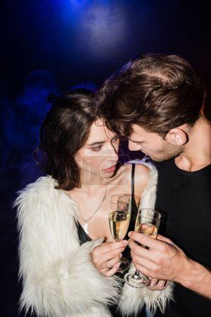 Man and seductive woman toasting with glasses of champagne, while looking at each other with backlit on black