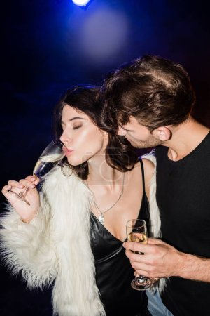 Photo for Passionate man looking at sexy brunette woman with closed eyes drinking champagne with backlit on black - Royalty Free Image